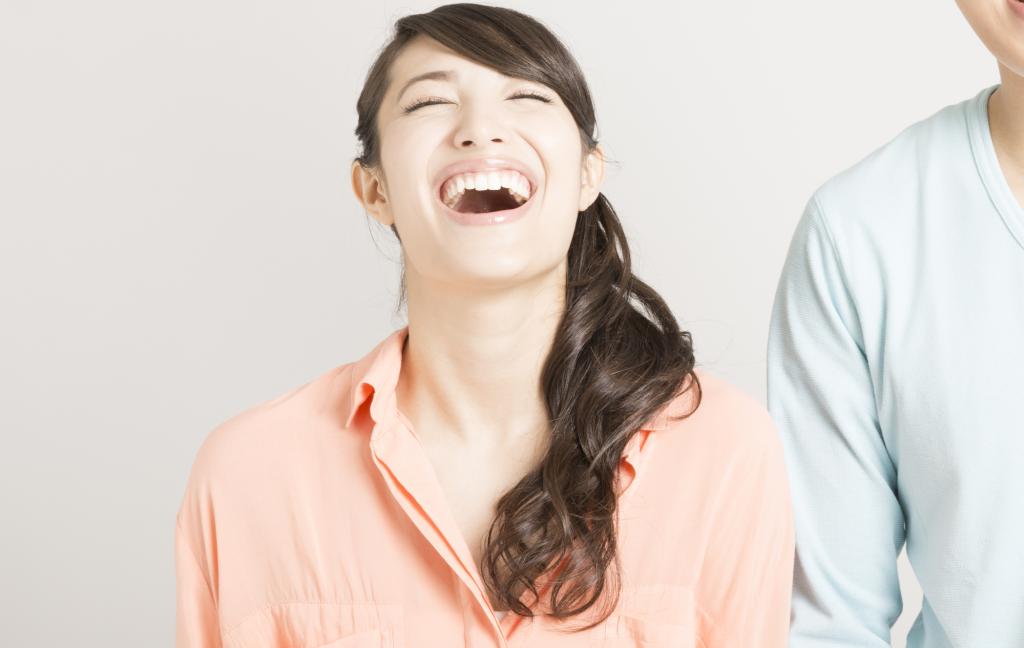 大きく口を開けて笑う女性